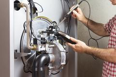 Plumber repairing a condensing boiler in the boiler room Stock Photos
