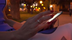 Girl in dress with red nail polish using her smartphone on evening street. 4K Stock Footage