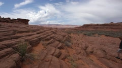 A man hiking up waves of sandstone in the desert Stock Footage