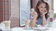 Young woman eating dessert in outdoors cafe. Stock Footage