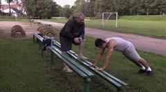 Young athlete do push ups near trainer on stadium Stock Footage
