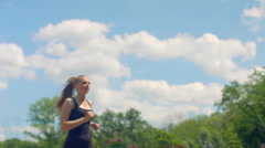 Fitness woman running in slow motion. Girl runs on sky background Stock Footage