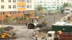 Workers apply hot asphalt near new building Stock Footage