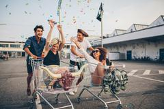 Young friends racing with shopping carts Stock Photos
