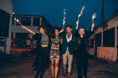 Friends enjoying nighttime party with sparklers in city Stock Photos