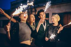 Young people enjoying new years eve with fireworks Stock Photos