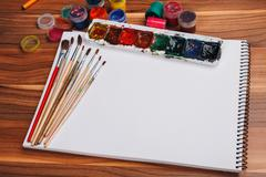 Album for sketches, watercolor paints and brushes Stock Photos