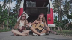 Hippie Girls Play Guitars Sitting on Road near Broken Minivan. Slow Motion Stock Footage