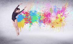 Modern street dancer jumping with colorful paint splashes Stock Photos