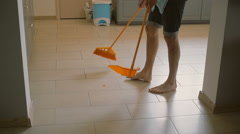 Young man, husband is sweeping the kitchen floor carefully with yellow Stock Footage