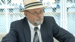 Portrait of an elderly man in hat, suit and glasses looking aside. 4K Stock Footage