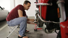 Serious young man repairing his motorcycle in garage Stock Footage
