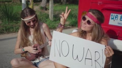 "Hippie Girls Sitting on a Road with a White Board ""No War"". Slow Motion Stock Footage"