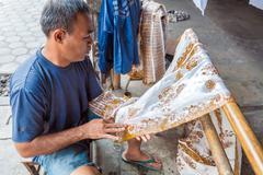 YOGYAKARTA, INDONESIA - AUGUST 28, 2008: Man painting wax at batik factory Stock Photos