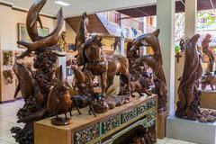 UBUD, INDONESIA - AUGUST 29, 2008: Carved wooden statues in souvenir shop Stock Photos