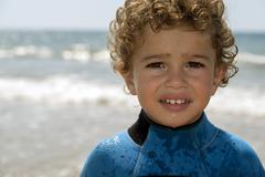 Portrait of playful boy on the beach with sea on background Stock Photos