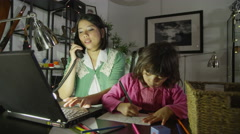 4K Mother working on her computer at night while daughter plays beside her Stock Footage