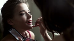 Makeup artist applying red lipstick to model lips Stock Footage