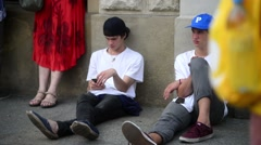 Two boys with mobile Sell Phones sitting at the sidewalk - Krakow Poland Stock Footage