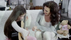 4K Mother and daughter spending time together and playing the guitar Stock Footage