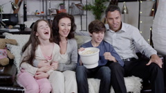 4K Happy family watching sports on t.v. and spilling popcorn everywhere Stock Footage