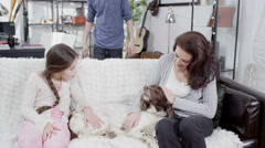 4K A mother and her children stroking the family dog on the sofa Stock Footage