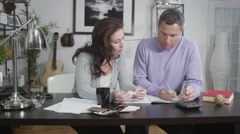 4K Attractive couple sit down to work out their household accounts Stock Footage
