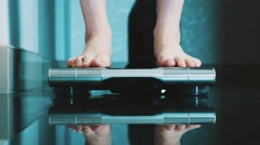 Woman put off slippers stand up on modern scales in apartment. Weighing Stock Footage