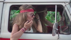 Hippie Girls Preen Sitting in a Car Cabin. Slow Motion Stock Footage