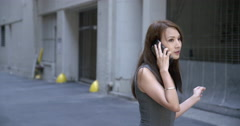 Beautiful Asian woman walks and talks on cellphone in alley 4K Stock Footage