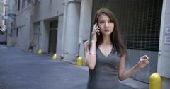 Beautiful Asian woman stands and uses cellphone in alley 4K Stock Footage