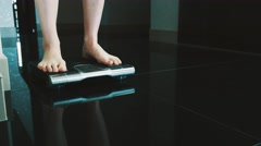 Woman walk on floor standing on modern scales in apartment. Weighing. Slimness Stock Footage