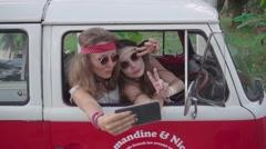 Hippie Girls Make Selfie Sitting in a Minivan Cabin. Slow Motion Stock Footage