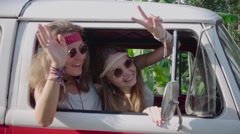 Hippie Girls Wave Out the Window Hands Sitting in a Car Cabin. Slow Motion Stock Footage