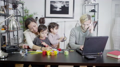 4K A busy father is working from home while his wife entertains their children Stock Footage