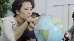 4K Attractive young parents using a globe to educate their children Stock Footage