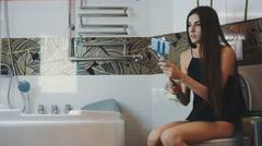 Girl sitting on toilet in bathroom. Take selfie on blue monopod. Posing Stock Footage