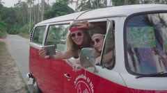 Hippie Girls Make Selfie Sitting in a Minivan Cabin. Slow Motion Stock Footage