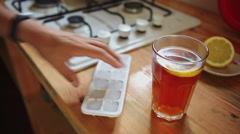 Man in the kitchen preparing tea with ice Stock Footage