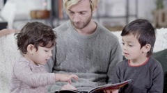 4K Loving father reading a story book with his 2 young sons Stock Footage