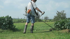 The worker cuts the grass using a lawnmower Stock Footage