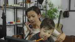 4K Busy mother working from home and taking care of her son Stock Footage