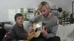 4K A father plays the guitar for his young son Stock Footage
