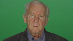 Older man disappointingly staring, on a green screen background Stock Footage