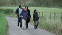 4K Happy family of 4 taking a walk along country lane Stock Footage