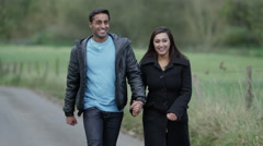 4K A man and woman holding hands and enjoying a walk down a country lane Stock Footage