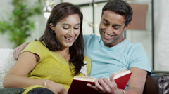 4K Attractive Indian couple spending time together and reading a book Stock Footage