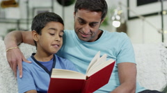 4K Father and son spending time together at home, reading a book Stock Footage
