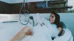 Brunette young girl taking bath full of foam in bathroom. Bathtub. Raise leg Stock Footage