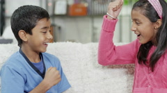 4K Brother and sister playing rock, paper, scissors at home Stock Footage